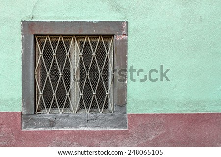 An old window on a facade painted with unusual colors.
