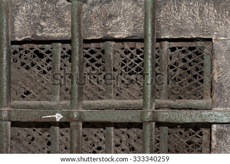 an old window with iron bars and fine mesh, covered with a century old dust   - stock photo