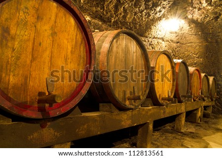 An old wine cellar with oak barrels - stock photo