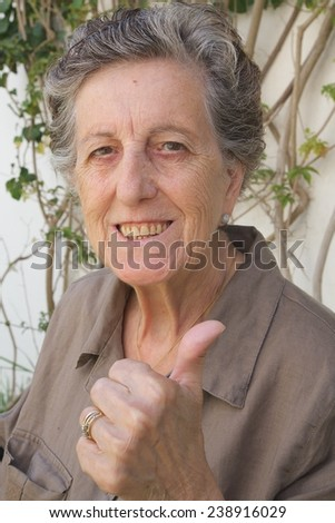 An old woman between 70 and 80 years old shows the thumb with a smile on her face expressing that everything is fine