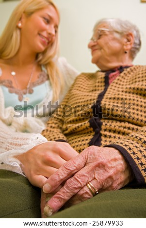 An old woman holding a younger person's hand (that could be a granddaughter, social worker; focus on hands) - part of a series. - stock photo
