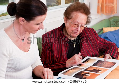 An old woman in a photo album scrolls - stock photo