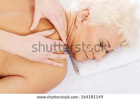 An old woman is having a massage. Spa concept.  Over white.  - stock photo