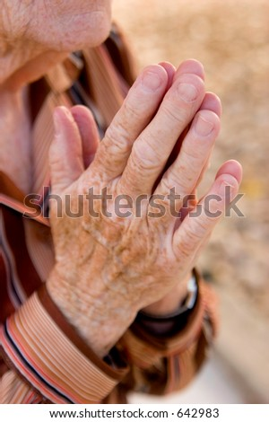 An old woman presses her hands together in prayer. - stock photo