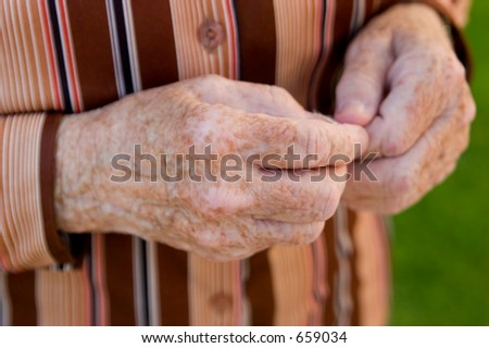 An old woman's speckled hands nervously fidgeting with a piece of nothing inbetween. - stock photo