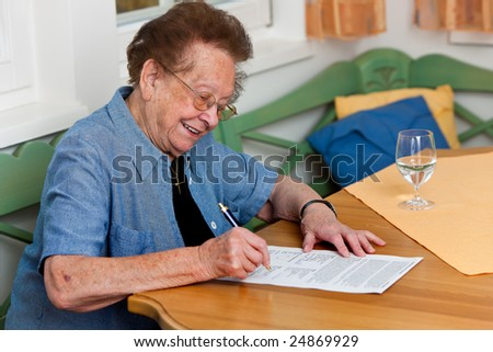An old woman signs a contract - stock photo