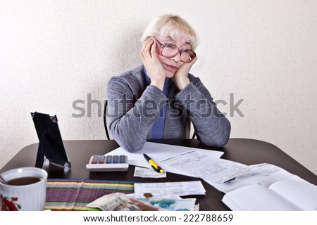 An old woman sits at a table laid out receipts - stock photo