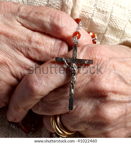 an old woman with rosario on the hands - stock photo