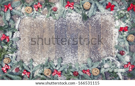 an old wooden background, decorated with pine branches, red loops and snow, a Christmas background - stock photo