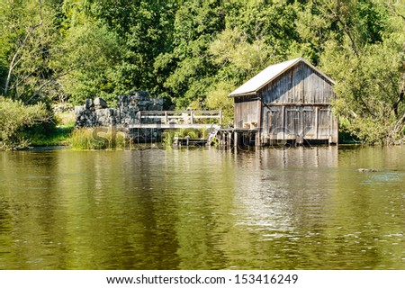 An old wooden boat house by the side of a creek.