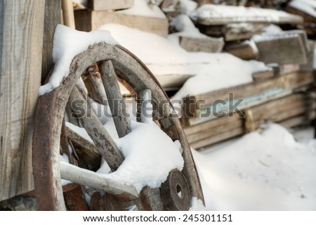 An old wooden cart wheel in snow - stock photo