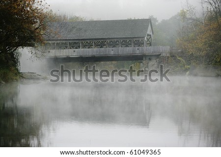 An old wooden covered bridge in Quechee Vermont, shrouded in fog.  The trees are in muted fall colors. - stock photo