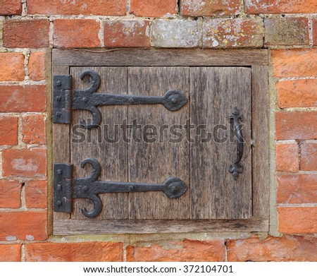 An Old Wooden Door with Black Metal Hinges in the Side of a wall in the Rural Village of Tintinhull in Somerset, England, UK