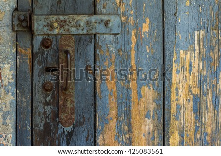An Old Wooden Door With Cracked Paint. Background. Handle With Keyhole. The Old Iron. - stock photo