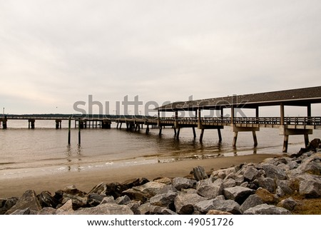 An old wooden fishing pier in the winter under cloudy skies