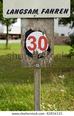 An old wooden 30 kilometers per hour speed limit sign - stock photo