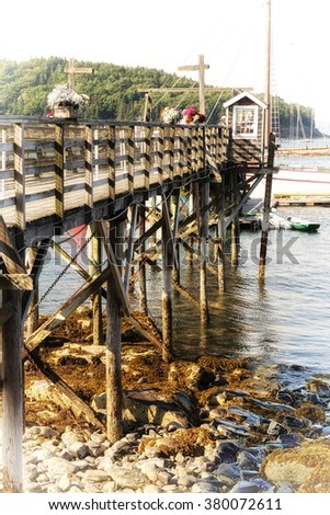 An old wooden pier in Bar Harbor, Maine.Filtered and processed to look like an old postcard.  - stock photo
