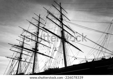 An old wooden sailing tea clipper with a view of the masts and rigging. A black and white image.Clear outline of the masts and rigging against the sky. - stock photo