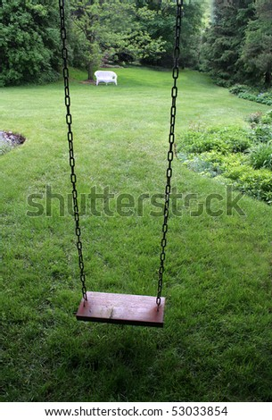 An old wooden swing sitting in a lush backyard. - stock photo