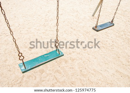 An old wooden swing sitting in the park - stock photo