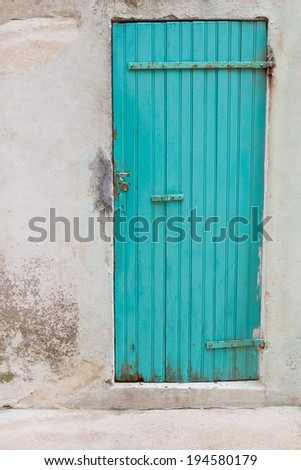 An old wooden turquoise or green door in a old house. - stock photo