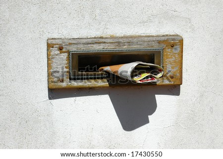 An old wooden vintage mailbox on white wall with newspaper in sunshine - stock photo