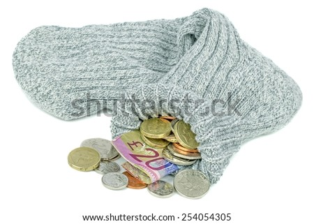 An old woolen sock full of British money on a white background - stock photo