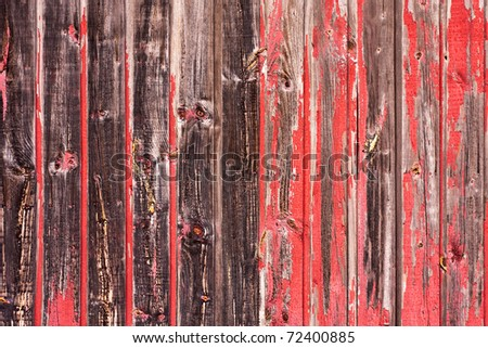 An old worn barn or antique wooden fence with chipped red paint. - stock photo