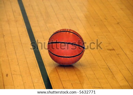 An old worn basketball on an indoor court - stock photo