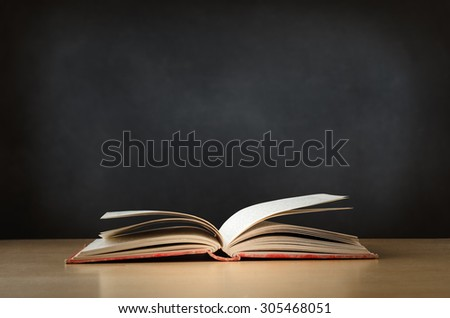 An old, worn, fabric covered red text book, lying opened on a school or college classroom desk.  Blackboard background provides copy space. - stock photo