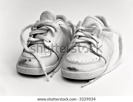 An old worn pair of white baby -  toddler shoes.