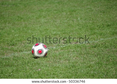 An old, worn soccer ball on a chalk line on a soccer field - stock photo