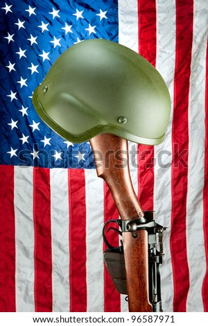 An old WWII Enfield rifle with helmet against an American flag, a memorial to fallen US soldiers - stock photo