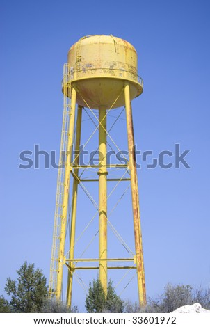 An old yellow water tower with graffiti against a blue sky. - stock photo