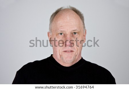 An older bald man in a black shirt looking stern
