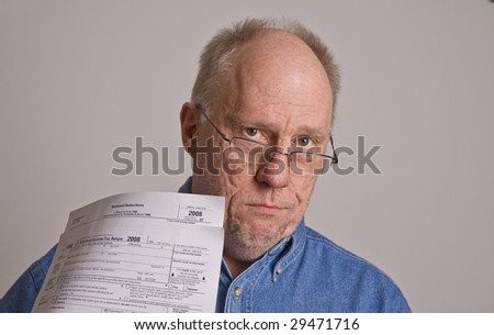 An older bald man in a blue denim shirt on a grey background wearing glasses and holding tax forms