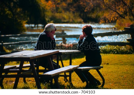An older couple sitting on a bench. - stock photo