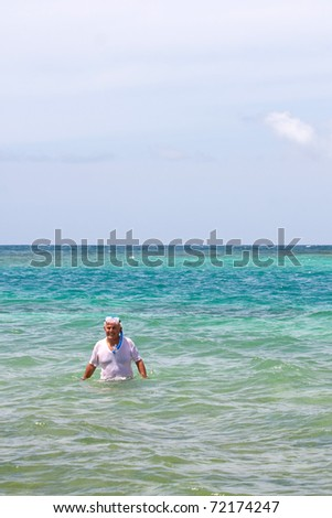 An older elderly man snorkels in tropical waters in the Caribbean off of the Puerto Rican island of Culebra. - stock photo