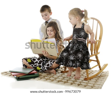 An older elementary girl reading books to her younger brother and sister.  Focus on reader.  On a white background.