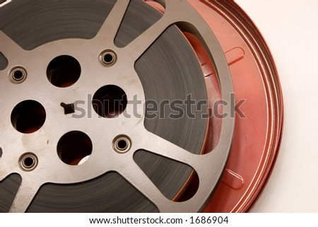 An older film canister and film reel wrapped tightly and precisely. - stock photo