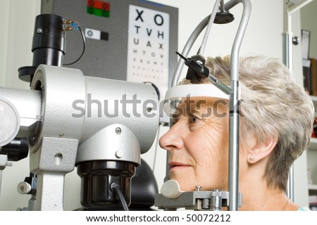 An older lady taking an eyesight test examination at an optician clinic