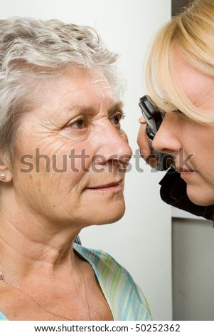 An older lady taking an eyesight test examination at an optician clinic - stock photo