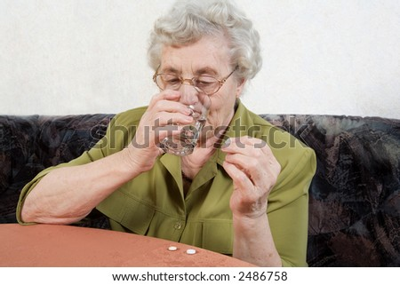 an older lady with a glass of water and tablet