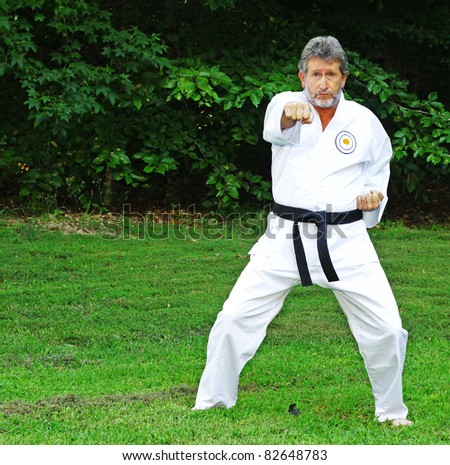 An older Male Black Belt practicing his Martial Arts punching outdoors in his backyard with room for your text - stock photo