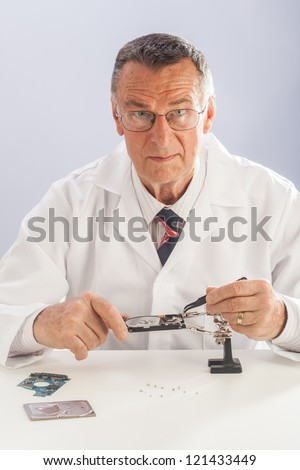An older male wearing a white lab coat and repairing electronic equipments, like a technician or a repair man. - stock photo