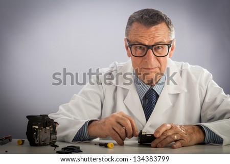 An older male wearing a white lab coat and repairing electronic equipments, like a technician or a repair man.