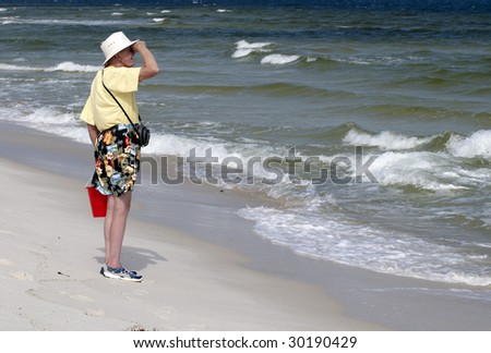 An older man exploring the beach alone.