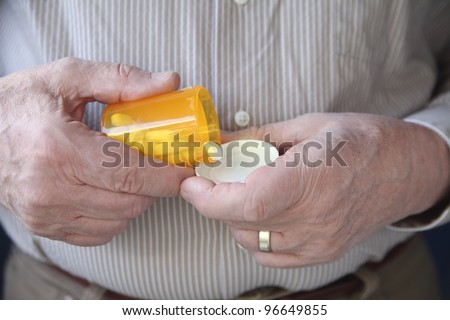 an older man gets ready to take a pill - stock photo