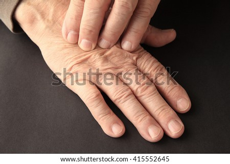 An older man has pain on his hand on a black background. - stock photo