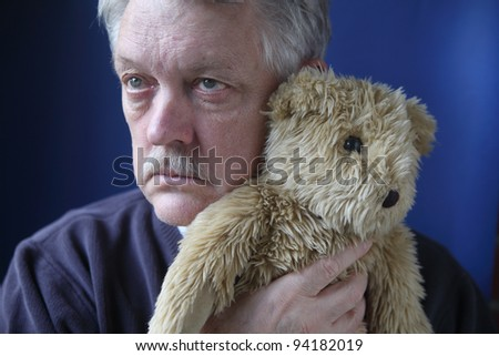 an older man holds a generic stuffed animal close to his face - stock photo